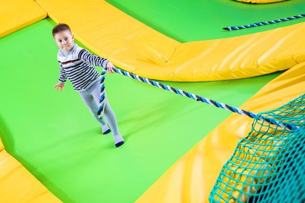 Kleiner junge, der im trampolinzentrum springt und mit seil klettert