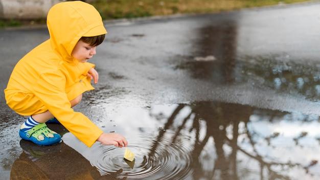 Kleiner junge, der im wasser mit einem papierboot spielt