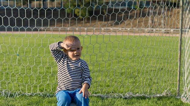 Kleiner junge, der in den torpfosten auf einem grünen grasbewachsenen fußballfeld sitzt und seine augen vor der späten abendsonne schützt