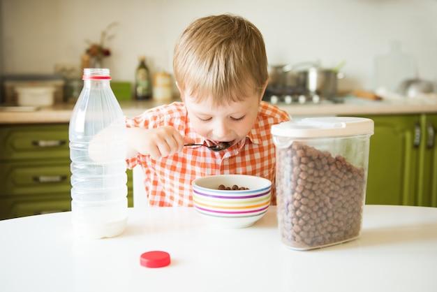 Kleiner junge, der in der küche saß und frühstückte, machte sich müsli