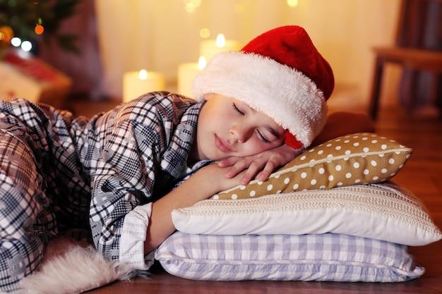 Kleiner junge, der in der nähe des kamins im zimmer schläft