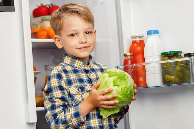 Kleiner junge, der in der nähe des offenen kühlschranks steht