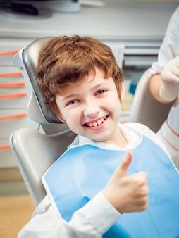 Kleiner junge, der in der zahnarztpraxis lächelt