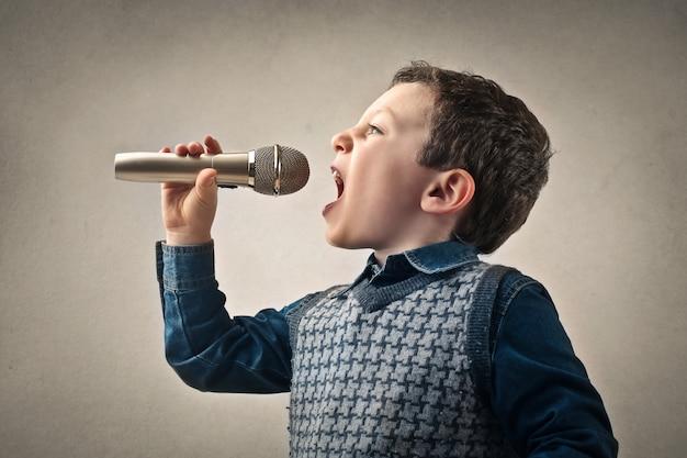 Kleiner junge, der in ein mikrofon singt
