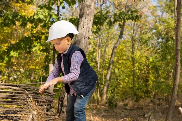 Kleiner junge, der in einem bauarbeiterhelm spielt, der im wald steht und einen zaun aus holzästen baut, mit kopienraum