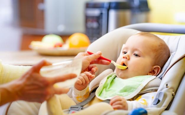 Kleiner junge, der in einem kindersitz sitzt und seinen löffel beißt