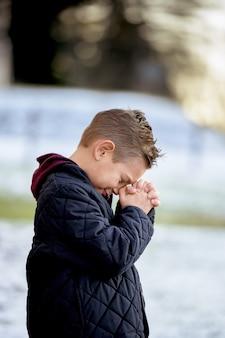 Kleiner junge, der in einem park steht und unter sonnenlicht mit einem verschwommenen hintergrund betet