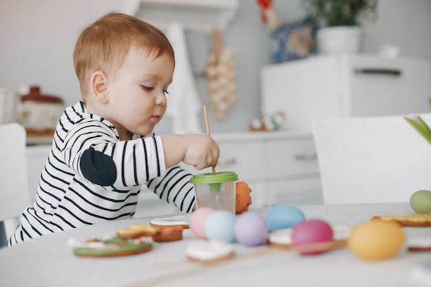 Kleiner junge, der in einer küchenmalerei sitzt