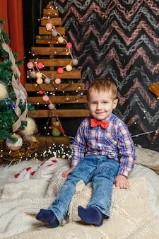 Kleiner junge, der in einer weihnachtsfotosession aufwirft