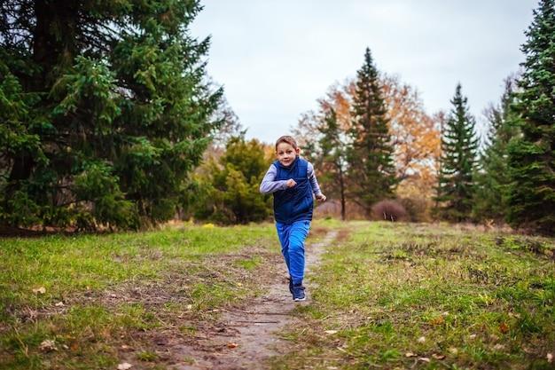 Kleiner junge, der in herbstwald läuft