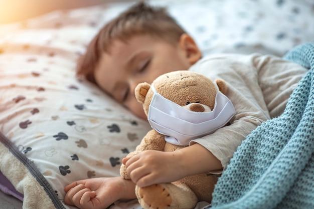 Kleiner junge, der in seinem bett mit seinem teddybär schläft, der eine maske trägt, um ihn gegen das konzept des corona-virus covid-19/2019-ncov zu schützen