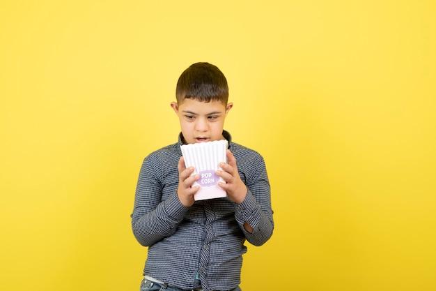 Kleiner junge, der innerhalb der schachtel des popcorns über gelb schaut.