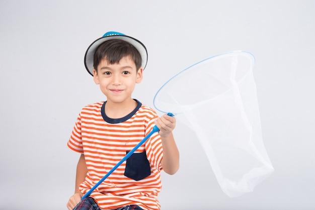 Kleiner junge, der insektennetz auf weißer wand nimmt