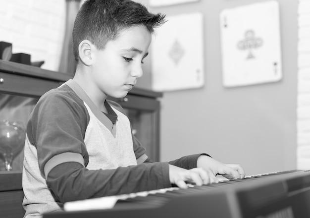 Kleiner junge, der klassisches klavier im wohnzimmer zu hause spielt
