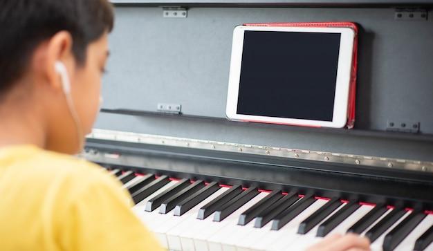 Kleiner junge, der klavier digitales digitales tablett zu hause übt