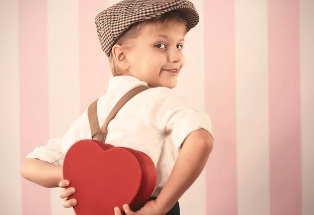 Kleiner junge, der kleines valentinsgeschenk hält