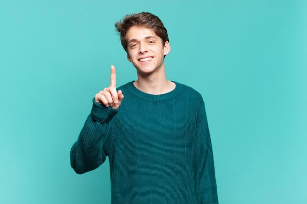 Kleiner junge, der lächelt und freundlich aussieht, nummer eins oder zuerst mit der hand nach vorne zeigt, herunterzählt