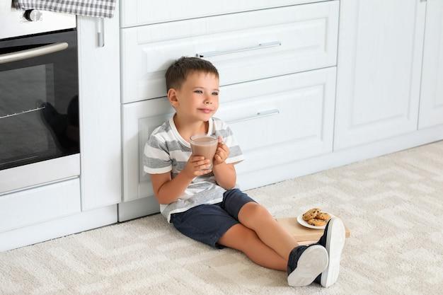 Kleiner junge, der leckere schokoladenmilch zu hause trinkt