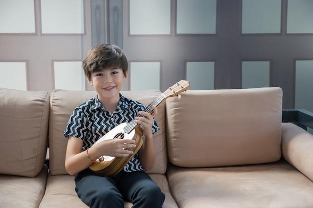 Kleiner junge, der lernt, die akustikgitarre zu spielen