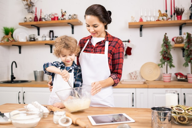 Kleiner junge, der lernt, eier für teig zu schlagen, während er nahe bei seiner mutter am tisch steht und ihr beim kochen hilft