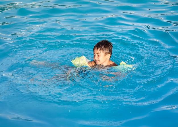 Kleiner junge, der lernt, im pool zu schwimmen