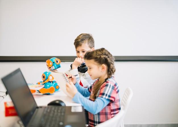 Kleiner junge, der mädchenzeichnung auf notizbuch mit stift im klassenzimmer betrachtet