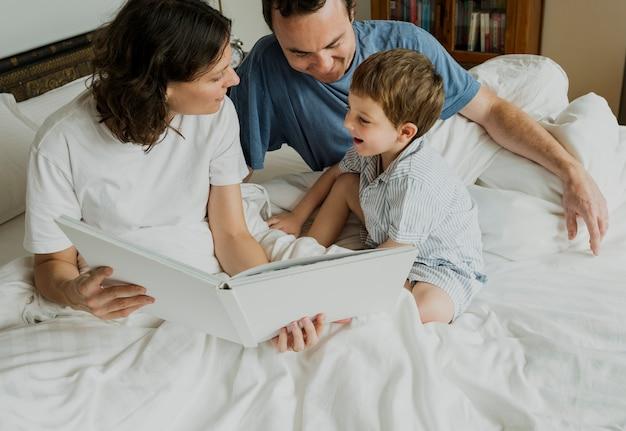 Kleiner junge, der mamma liest studie vor dem schlafen hört