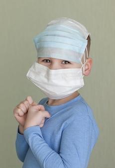 Kleiner junge, der medizinische gesichtsmaske zum gesundheitsschutz vor influenzavirus trägt.