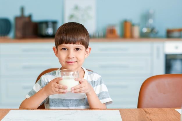 Kleiner junge, der milch in der küche trinkt