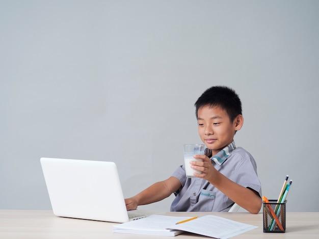 Kleiner junge, der milch trinkt, während er online zu hause studiert