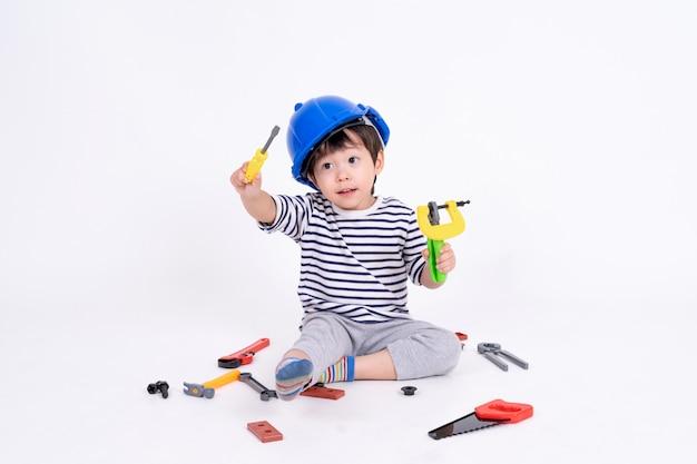 Kleiner junge, der mit baugeräten auf weiß spielt
