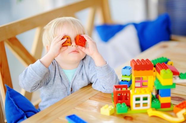 Kleiner junge, der mit bunten plastikblöcken am kindergarten oder zu hause spielt