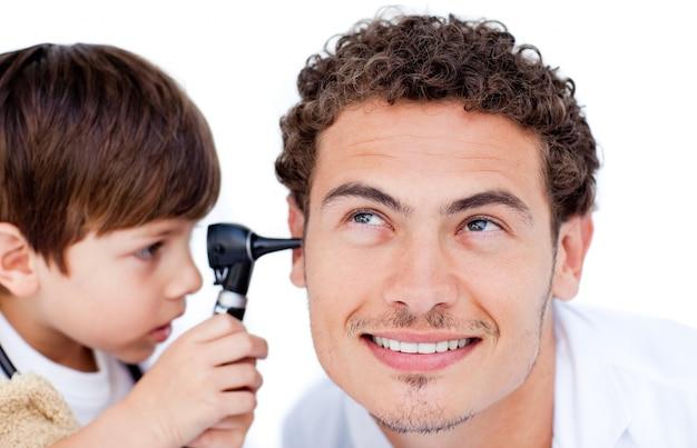 Kleiner junge, der mit dem doktor spielt