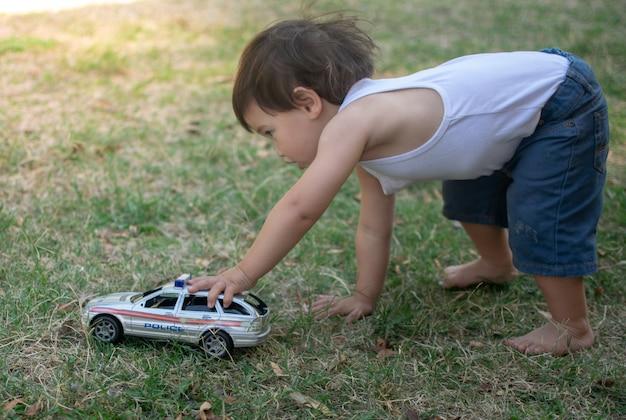 Kleiner junge, der mit dem polizeiwagen spielt