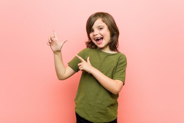 Kleiner junge, der mit den zeigefingern auf einen kopienraum zeigt und aufregung und wunsch ausdrückt