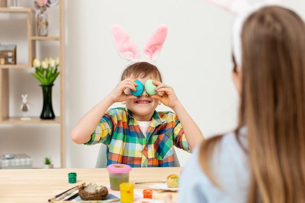 Kleiner junge, der mit eiern spielt