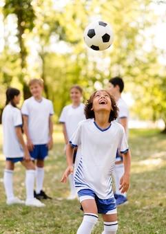 Kleiner junge, der mit einem fußball draußen neben anderen kindern spielt