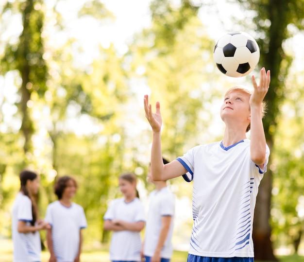 Kleiner junge, der mit einem fußball draußen spielt