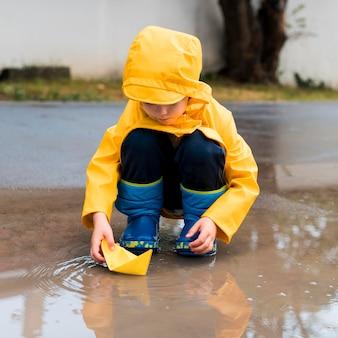 Kleiner junge, der mit einem gelben papierboot spielt