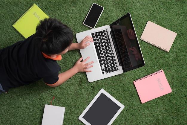 Kleiner junge, der mit einem laptop in der natur liegt