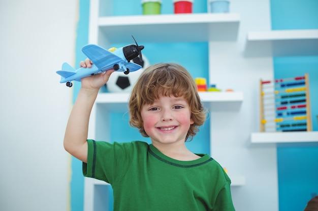 Kleiner junge, der mit einem spielzeugflugzeug spielt