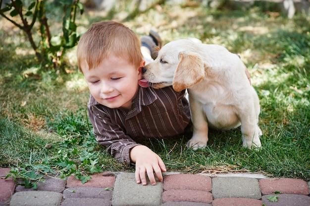 Kleiner junge, der mit einem weißen labrador-welpen spielt