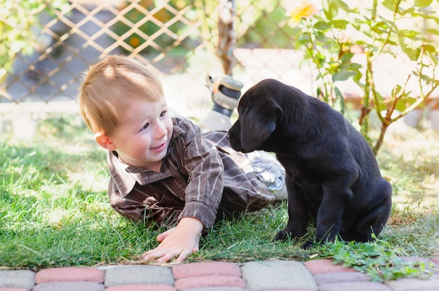 Kleiner junge, der mit einem welpen labrador im park spielt