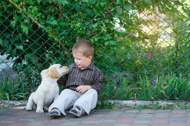 Kleiner junge, der mit einem welpenlabrador im park spielt