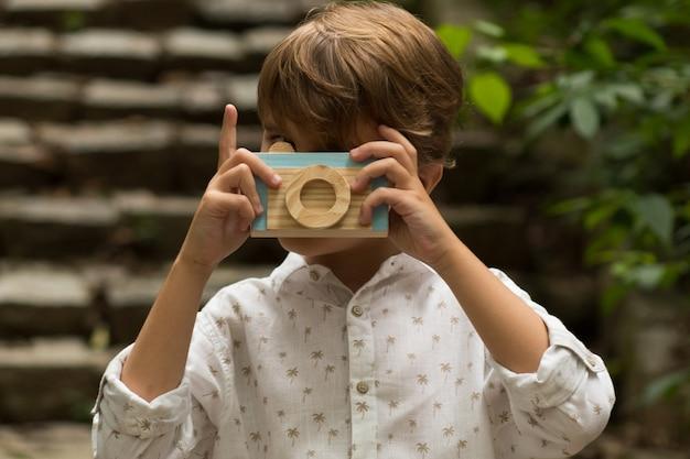 Kleiner junge, der mit einer hölzernen spielzeugkamera spielt. junge, der vortäuscht, ein foto am park zu machen.