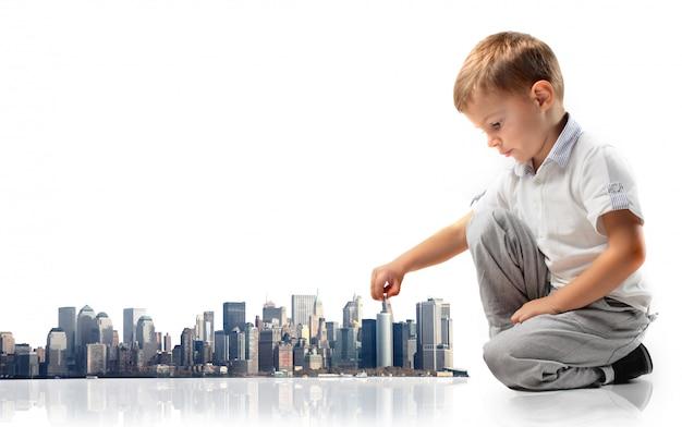 Kleiner junge, der mit einer stadtmaquette spielt