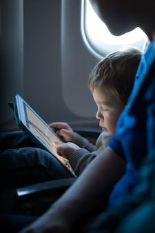Kleiner junge, der mit einer tablette in einem flugzeug spielt