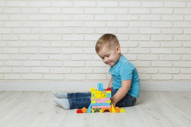 Kleiner junge, der mit erbauer auf weißem hintergrund spielt. baby, das blockspielwaren spielt