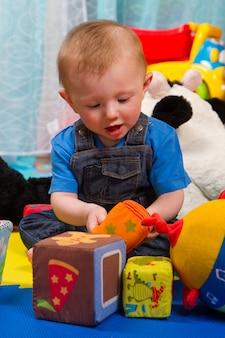 Kleiner junge, der mit farbigem weichem würfel spielt