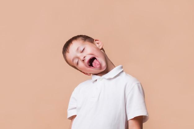 Kleiner junge, der mit geschlossenem auge auf beige hintergrund neckt